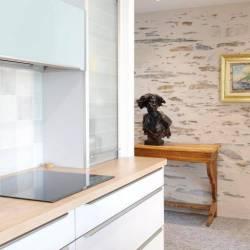 En cuisine, vue latérale sur le dégagement traité à pierres vues.